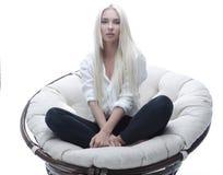 Schöne junge Frau, die auf der Couch in einem großen bequemen Lehnsessel sitzt Lizenzfreie Stockfotografie