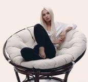 Schöne junge Frau, die auf der Couch in einem großen comfortabl sitzt Stockbild