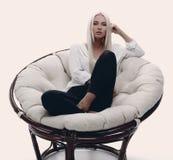 Schöne junge Frau, die auf der Couch in einem großen comfortabl sitzt Stockfotografie