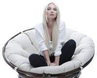 Schöne junge Frau, die auf der Couch in einem großen comfortabl sitzt Lizenzfreie Stockfotos
