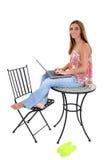 Schöne junge Frau, die auf der Tabelle arbeitet an Laptop sitzt Stockfotografie