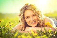 Schöne junge Frau, die auf einem Feld liegt stockbilder