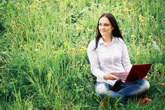 Schöne junge Frau, die auf einem Gras sitzt Stockfotografie