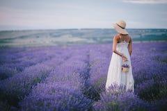 Schöne junge Frau, die auf einem Lavendelgebiet aufwirft