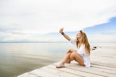Schöne junge Frau, die auf einem Pier sitzt und ein Selbst-portra nimmt Lizenzfreie Stockfotos