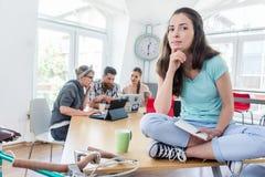 Schöne junge Frau, die auf einem Schreibtisch während der Arbeit sitzt Lizenzfreies Stockfoto