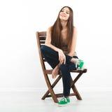 Schöne junge Frau, die auf einem Stuhl sitzt stockbild