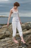 Schöne junge Frau, die auf einen felsigen Strand geht Lizenzfreies Stockfoto