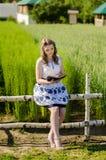 Schöne junge Frau, die auf einer Anmeldung ein Feld sitzt Lizenzfreies Stockfoto