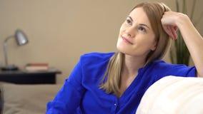 Schöne junge Frau, die auf einer Couch sitzt und von etwas gut und positiv träumt Genießen des Lebens stock footage
