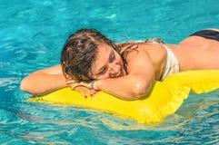 Schöne junge Frau, die auf einer gelben aufblasbaren Matratze sich entspannt Stockbild