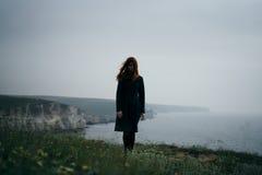 Schöne junge Frau, die auf einer Klippe eines Berges nahe dem Meer steht Stockbilder