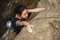 Schöne junge Frau, die auf Felsen klettert Stockbilder