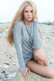 Schöne junge Frau, die auf Felsen sitzt Stockfoto