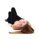 Schöne junge Frau, die auf Fußboden legt Stockbild
