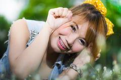 Schöne junge Frau, die auf Gras mit Blumen liegt Lizenzfreie Stockfotografie