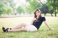 Schöne junge Frau, die auf Gras sitzt Stockbild