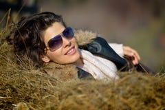 Schöne junge Frau, die auf Heustapel sich entspannt Lizenzfreie Stockfotografie