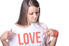Schöne junge Frau, die auf ihr weißes t-shir zeigt lizenzfreie stockfotografie