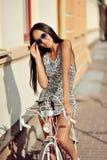 Schöne junge Frau, die auf ihrem Fahrrad sitzt Lizenzfreie Stockfotos