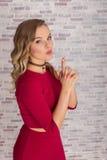 Schöne junge Frau, die auf ihrem Faustfeuerwaffezeichen mit ihren Fingern für sexy Geschäftskampf durchbrennt lizenzfreie stockbilder