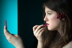 Schöne junge Frau, die auf Lippenstift sich setzt Lizenzfreies Stockbild
