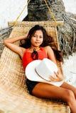 Schöne junge Frau, die auf Rattanhängematte auf dem weißen Sandstrand während der Reiseferien sich entspannt Lizenzfreies Stockfoto