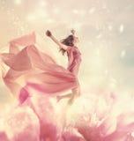 Schöne junge Frau, die auf riesige Blume springt Lizenzfreie Stockfotos
