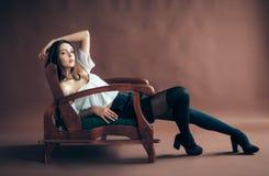 Schöne junge Frau, die auf Sofa auf braunem Hintergrund aufwirft Fashio stockbilder