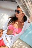 Schöne junge Frau, die auf Sonnenichtstuer liegt lizenzfreie stockfotos