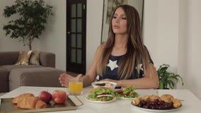 Schöne junge Frau, die auf Tabelle mit mittlerem Schuss des appetitanregenden geschmackvollen Frühstücks sitzt stock video footage