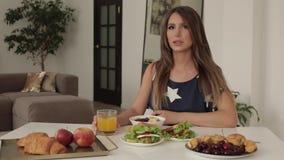 Schöne junge Frau, die auf Tabelle mit mittlerem Schuss des appetitanregenden geschmackvollen Frühstücks sitzt stock video