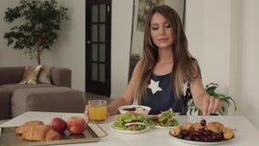 Schöne junge Frau, die auf Tabelle mit mittlerem Schuss des appetitanregenden geschmackvollen Frühstücks sitzt stock footage