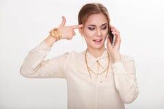Schöne junge Frau, die auf Telefon und Spielen mit ihrem Haar spricht Überraschung und Freude Stockfotografie