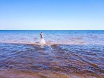 Schöne junge Frau, die auf transparentem Wasser läuft lizenzfreie stockfotografie