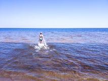 Schöne junge Frau, die auf transparentes Wasser geht stockfoto