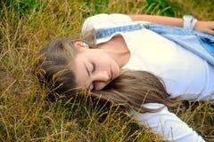 Schöne junge Frau, die auf trockenem Gras liegt Stockfotografie