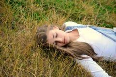 Schöne junge Frau, die auf trockenem Gras liegt Lizenzfreie Stockbilder