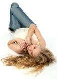 Schöne junge Frau, die auf weißen Fußboden legt Lizenzfreie Stockfotografie
