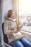 Schöne junge Frau, die auf Zugsitz sitzt Stockbild