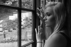 Schöne junge Frau, die aus einem Fenster heraus anstarrt lizenzfreies stockfoto