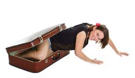 Schöne junge Frau, die aus Koffer heraus steigt Stockbild