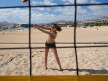 Schöne junge Frau, die beachvolleyball spielt Stockfotos