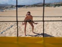 Schöne junge Frau, die beachvolleyball spielt Lizenzfreie Stockfotos