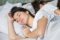 Schöne junge Frau, die bequem im gemütlichen Bett mit boyf schläft lizenzfreie stockfotos