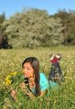 Schöne junge Frau, die in blühender Wiese liegt Lizenzfreies Stockfoto