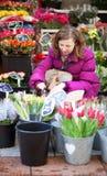Schöne junge Frau, die Blumen auswählt Lizenzfreies Stockbild