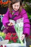 Schöne junge Frau, die Blumen auswählt Lizenzfreies Stockfoto
