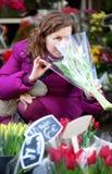 Schöne junge Frau, die Blumen auswählt Lizenzfreie Stockbilder
