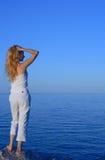 Schöne junge Frau, die das Meer betrachtet Lizenzfreies Stockfoto